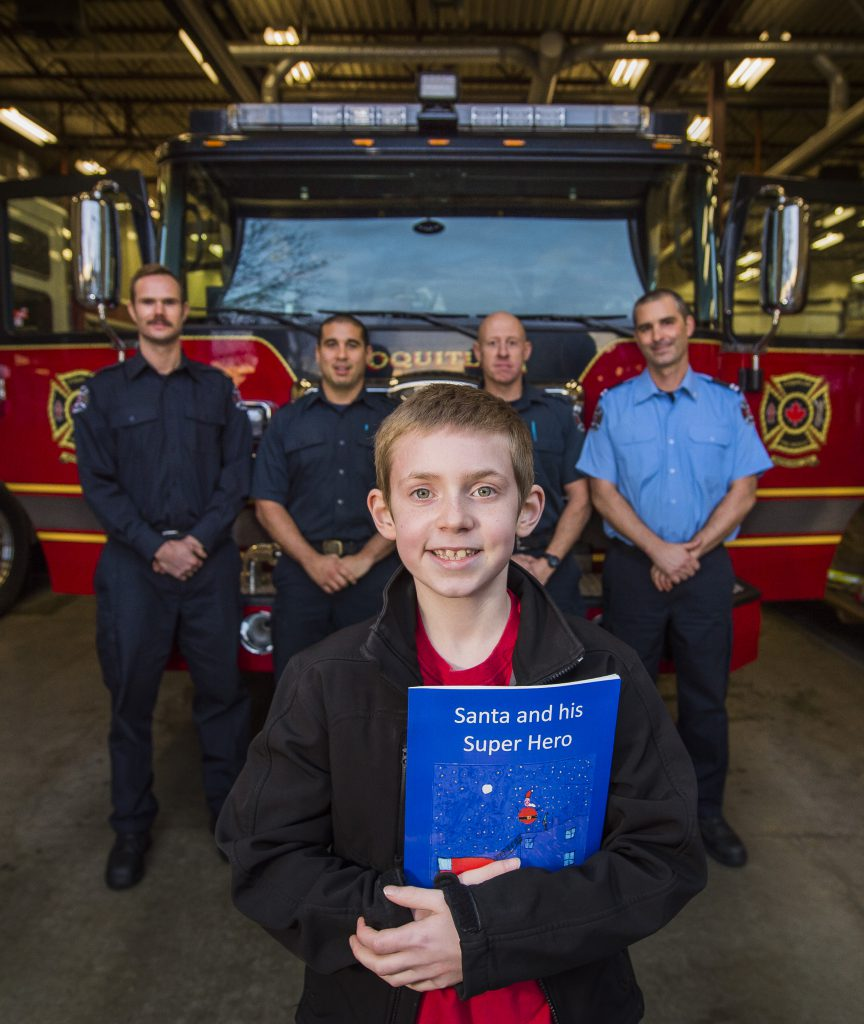 COQUITLAM,BC:NOVEMBER 29, 2016 -- Nathan McTaggart poses for a photo with the book and members of the Austin Heights Fire Station in Coquitlam, BC, November, 29, 2016. Nathan wrote about Santa getting stuck in the chimney and firefighters had to rescue him. (Richard Lam/PNG) (For Tracy Sherlock) 00046527A [PNG Merlin Archive]